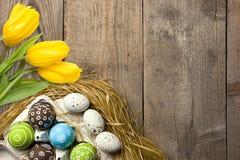 Ostern-Karte mit bunten Eiern im Nest und gelben Tulpen über hölzernem Hintergrund Draufsicht mit Kopienraum stockbild