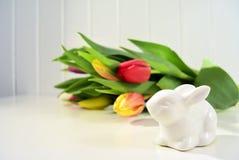 Ostern-Konzept, Frühlingstulpen und Porzellanhäschen Stockbild