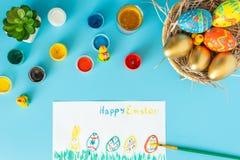 Ostern-Konzept, Korb mit handgemachten Ostereiern nahe bei Mehrfarbenfarbenb?rste und Wei?buch mit Zeichen fr?hliche Ostern und F lizenzfreie stockfotos