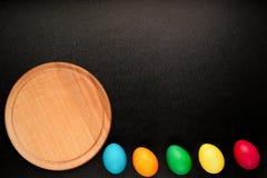 Ostern-Konzept malte Eier auf schwarzem Hintergrund in der Reihe für holid Stockfotografie