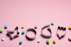 Ostern-Konzept, Plätzchen-Schneider und Schokoladen-Eier auf rosa Hintergrund stockfoto