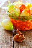 Ostern-Korb, Eier und Häschen auf hölzernem Vorstand Stockfoto