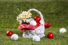 Ostern-Korb mit Golfbällen und Blumen Stockfotos