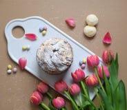 Ostern-Kuchen mit Blumen und den Blumenblättern auf keramischem Schneidebrett stockfoto