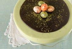 Ostern-Kuchen mit Tee matcha verzierte Schokoladenganache und -materialeier Stockfotografie