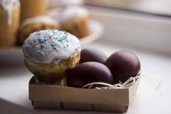 Ostern-Kuchen und bunte Ostereier auf einem Fensterbrett in einem Docht Lizenzfreies Stockbild