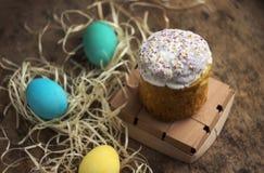 Ostern-Kuchen und bunte Ostereier auf einem Holztisch in einem wic Lizenzfreie Stockbilder