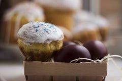 Ostern-Kuchen und bunte Ostereier auf einem Holztisch in einem wic Lizenzfreie Stockfotos