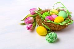Ostern-Nest mit gemalten Eiern und Tulpen, Kopienraum lizenzfreies stockfoto