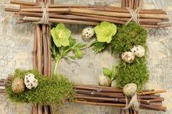 Ostern-Rahmen mit Weinlesehintergrund und sieben kochten Wachteleier plus zwei Helleboreblumen Stockfoto