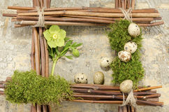 Ostern-Rahmen mit Weinlesehintergrund und -wachteln kochte Eier und Helleboreblume Stockfotos