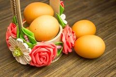 Ostern-Russestillleben Eier in einem Blumenkorb, Bonbons, Rollen, bereiteten sich für Rest auf einem hölzernen Hintergrund vor Stockbilder