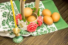 Ostern-Russestillleben Eier in einem Blumenkorb, Bonbons, Rollen, bereiteten sich für Rest auf einem hölzernen Hintergrund vor Lizenzfreie Stockbilder
