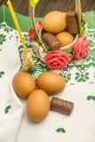 Ostern-Russestillleben Eier in einem Blumenkorb, Bonbons, Rollen, bereiteten sich für Rest auf einem hölzernen Hintergrund vor Stockfotos
