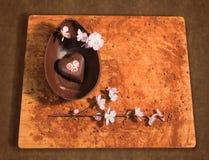 Ostern-Schokoladenei mit einer Überraschung eines verzierten Herzens, besprüht mit Kakaopulver, Schokoladensplitter und Mandel bl Stockbild