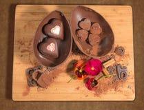 Ostern-Schokoladenei und -herzen verziert mit Kakaopulver und Blumen Lizenzfreie Stockfotos