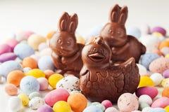 Ostern-Schokoladenfiguren auf buntem Schokoladeneihintergrund stockfotos