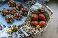 Ostern-Stillleben mit roten Eiern und Ostern backt zusammen lizenzfreie stockbilder