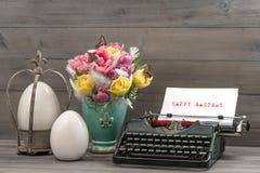 Ostern-Stillleben mit Tulpen, Eiern und Schreibmaschine Stockbilder