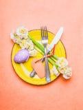 Ostern-Tabellengedeck mit Narzissenblumen, Tischbesteck, Platte, Eier und leeren Aufkleberkarte auf Pastellrosahintergrund, Drauf Stockfotografie