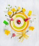 Ostern-Tischschmuck mit rotem Ei, Frühlingsblumen, Zeichen, Messer und Gabel auf gelber Platte lizenzfreies stockfoto