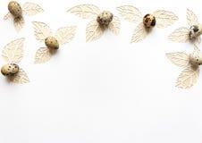 Ostern-Wachteleier auf einem weißen Hintergrund, Blätter schnitten vom Papier Stockfotografie