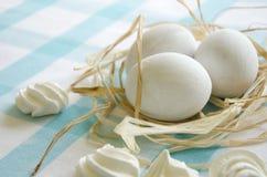 Ostern-weiße Eier und -meringe auf einer blauen Tischdecke Stockfotos