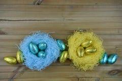 Ostern-Zeit mit glänzenden eingewickelten SchokoladenOstereiern in einem Nest in den blauen und goldenen gelben Farben mit Raum Stockfotografie