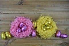 Ostern-Zeit mit glänzenden eingewickelten SchokoladenOstereiern in einem Nest in den rosa und goldenen gelben Farben Lizenzfreie Stockfotos