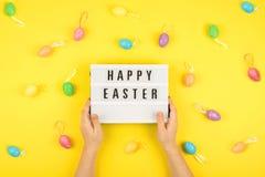 Ostern-Zusammensetzung, Grußkarte mit der Kinderhand, lightbox Text fröhliche Ostern, farbige dekorative Eier auf Farbhintergrund lizenzfreie stockfotografie