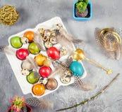 Ostern-Zusammensetzung mit farbigen Eiern und Dekorationen Stockbild