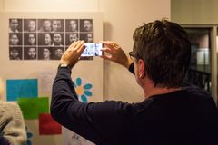 Refugees are telling their stories in the exhibition Angekommen. Ostfildern, Germany - February 23, 2018: A man is taking a photo of the participating refugees Royalty Free Stock Image