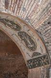 Ostia Antica, Italien - April 23, 2009 - röd tegelsten fördärvar med en design för mosaiktegelplatta i en valvgång i den arkeolog Royaltyfri Foto
