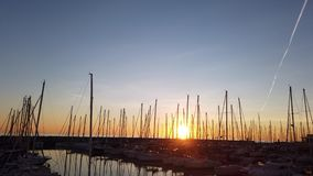 Sunset time lapse in golden hour at tourist harbor in Rome, Many sailboats are moored, some planes leave their trails in the sky. Ostia Lido Rome, Italy stock video footage