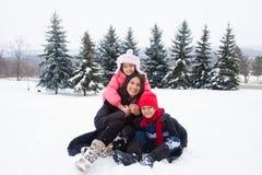 Ostinderfamilie, die im Schnee spielt Lizenzfreie Stockbilder