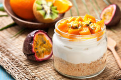 Ostkaka i en krus med mango och passionfruit Royaltyfri Bild