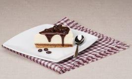 Ostkaka med chokladsås på den vita plattan arkivbild