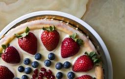 Ostkaka med jordgubbar och blåbär på marmorerar tabellen arkivbilder