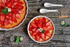 Ostkaka med jordgubbar och nya blommor, jordgubbar på en trätabell Fotografering för Bildbyråer