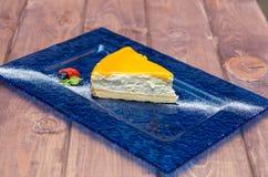 Ostkaka med mangosås, passionfrukt på en blå bakgrund Royaltyfria Bilder