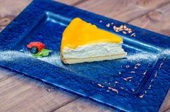 Ostkaka med mangosås, passionfrukt på en blå bakgrund Royaltyfria Foton