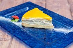 Ostkaka med mangosås, passionfrukt på en blå bakgrund Arkivfoton