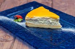Ostkaka med mangosås, passionfrukt på en blå bakgrund Royaltyfri Bild
