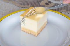 Ostkaka på den vita plattan med gaffeln Royaltyfri Fotografi