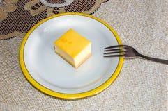 Ostkaka på den vita plattan med gaffeln Royaltyfri Foto