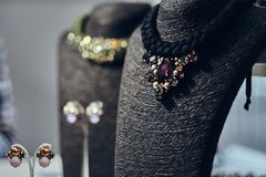 Necklaces with gemstones on a black jewelry bust in a store. Ostly necklaces with gemstones on a black jewelry bust in a store stock image