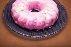 Ostmassakaka som dekoreras med rosa glasyr på en blå platta royaltyfria bilder
