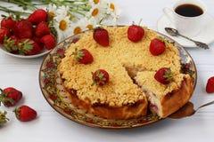 Ostmassakakan med jordgubbar med för snitt ett stycke ut av kakan lokaliseras på en vit bakgrund royaltyfri fotografi