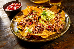 Ostnachos med nötkött, guacamole och salsa royaltyfri foto