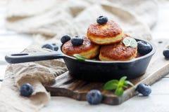Ostpannkakor och blåbär i gjutjärnpanna Royaltyfri Foto